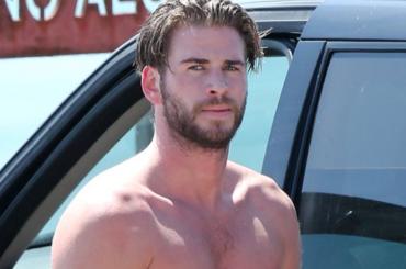 Liam Hemsworth, spuntano le chiappe dalla muta da surf – foto